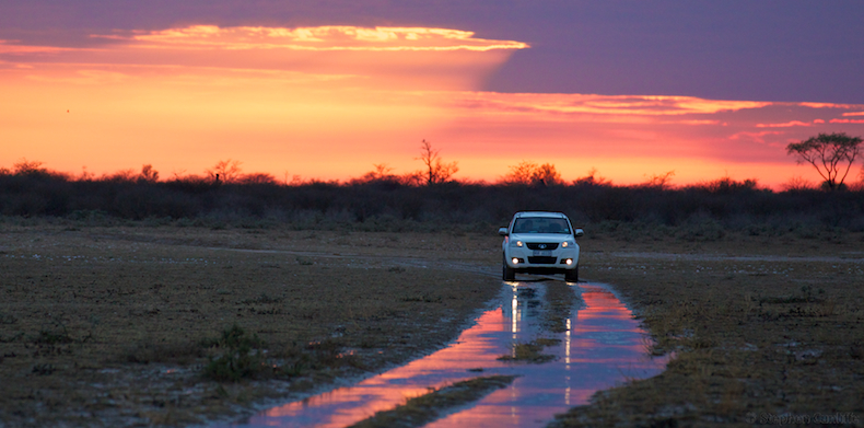 Driving across Marushele Pan under a fiery sky after the first big rains